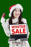 Attractive girl online shopping in winter sale time. Young girl wearing winter clothes, online shopping with credit card and laptop in winter sale time Royalty Free Stock Photo
