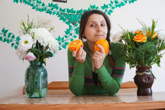 Attractive girl with oranges. Young attractive girl at home, sitting at the table with the flowers and holding oranges The girl looks very happy Royalty Free Stock Photos