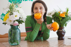 Attractive girl with oranges. Young attractive girl at home, sitting at the table with the flowers and holding oranges The girl looks very happy Stock Images