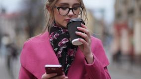 Attractive girl outside the house, standing in the city-center having a cup of coffee and texting message. Being online. Virtual reality. Rotation view, slow stock video