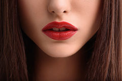 Attractive girl with perfect make-up. Close up of voluptuous female red lips. Woman has long brunette hair Royalty Free Stock Photo