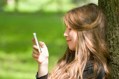 Attractive girl with phone in park. Portrait of attractive girl is sitting with mobile phone in park and typing or reading sms Royalty Free Stock Photo