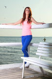 Attractive girl on pier Young woman and sea Stock Photo