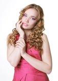 Attractive girl in pink dress. Studio. Attractive girl touching face in pink dress. Studio shot Stock Photos