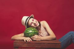 Attractive girl with pink make up, wearing jeans, hat and top, posing at red studio background near wooden box, holding watermelon. Looking at camera and smile stock image