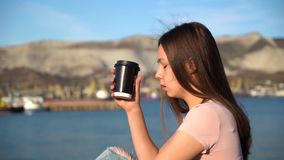 Attractive girl in pink t-shirt sitting on railing on embankment and drink coffee from black cup. Attractive girl in pink t-shirt sitting on railing on stock video
