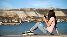 Attractive girl in pink t-shirt sitting on railing on embankment and drink coffee from black cup. Attractive girl in pink t-shirt sitting on railing on stock video footage