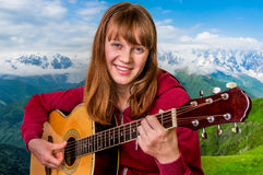 Attractive girl playing acoustic guitar. On nature background Royalty Free Stock Images
