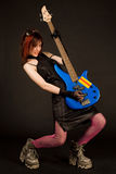Attractive girl playing bass guitar. Isolated on black background royalty free stock photo