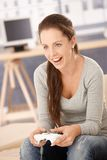 Attractive girl playing computer game at home. Attractive young girl playing computer game at home, having fun, laughing Royalty Free Stock Image
