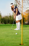 Attractive girl playing golf Royalty Free Stock Image