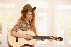 Attractive girl playing on guitar. Dressed in country style Stock Photos