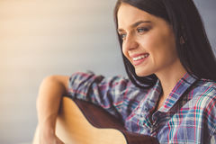 Attractive girl playing guitar. Portrait of attractive young girl with a guitar smiling, on gray wall background Stock Photography