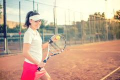 Attractive girl playing tennis and smiling at camera. Healthy modern lifestyle with sportswoman and accesssories. Attractive brunette playing tennis and smiling royalty free stock photo