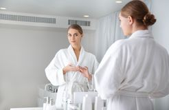 Attractive girl posing in front of the mirror in bathroom. I am beautiful. Portrait of confident young woman looking at mirror with satisfaction while standing stock images