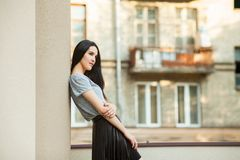 Attractive girl posing near building. Attractive young girl posing near building. slim woman in a gray shirt and a black leather skirt walking around city Royalty Free Stock Photo