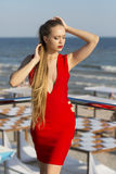 An attractive girl posing on a terrace on a blue sea background. A lady in a bright red dress. A woman with amazing long hair. royalty free stock image