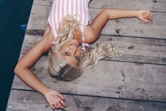 Attractive girl posing on wooden pier royalty free stock image