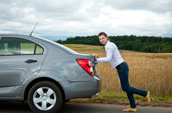 Attractive girl pushing her car stopped Royalty Free Stock Photography