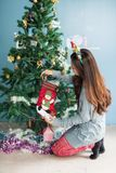 Attractive girl put xmas gifts in socks. Asian girl put gifts in socks to attach on Xmas tree. Attractive cute Chinese woman dressed as Santa to celebrate stock photos