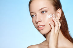 Attractive girl puts on the skin cream. Royalty Free Stock Photos
