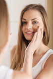 Attractive girl putting anti-aging cream. Stock Photos