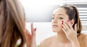 Attractive girl putting anti-aging cream Royalty Free Stock Photography