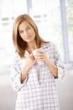 Attractive girl in pyjama drinking tea smiling Stock Image