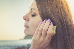 Attractive girl in rays of setting sun listening to noise of shell. Summer, vacation, dream theme. Attractive girl in rays of setting sun listening to noise of stock photos