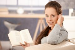 Attractive girl reading book on sofa at home. Young attractive girl reading book at home, sitting on sofa, smiling Stock Image