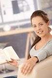Attractive girl reading book on sofa at home Stock Images