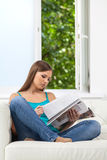 Attractive girl reading magazine on sofa. Royalty Free Stock Photography