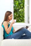 Attractive girl reading magazine on sofa. Royalty Free Stock Image