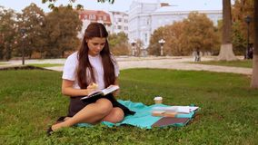 Attractive girl reads novel outdoors. Happy student or businesswoman has break reading book eating lunch in city park Young caucasian brunette with long hair stock footage