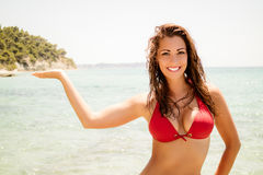 Attractive Girl In A Red Bikini. Beautiful young woman posing in red bikini on the beach. She is smiling and looking at camera stock image