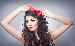 Attractive girl with a red bow on her head and red bra send a kiss.Pinup model on grey background.Beautiful pinup model. Head shot with red bra and smiling Stock Image