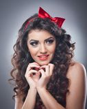 Attractive girl with a red bow on her head and red bra send a kiss.Pinup model on grey background.Beautiful pinup model. Head shot with red bra and smiling Stock Images