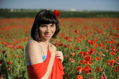 Attractive girl in a red cloth among poppies Stock Photo