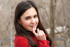 Attractive girl in red coat and her playful look Royalty Free Stock Photos
