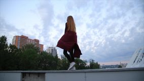 Attractive girl in a red coat with red lips goes by the street in a city than turns to camera and smiles. stock footage