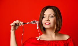 Attractive girl in red dress holding a fork in hands. on the headphone plug. prepared to eat. stock photos