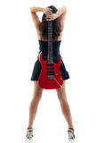 Attractive girl with red guitar behind her back. Attractive girl in black miniskirt from behind, holding a red electric guitar behind her back, isolated on white Royalty Free Stock Photography