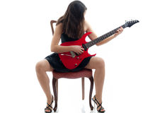 Attractive girl with red guitar sitting on a chair Royalty Free Stock Photo
