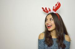 Attractive girl with reindeer horns on her head looks your product excited on gray background. Copy space Stock Images