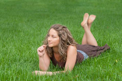 Attractive girl relaxes on grass Royalty Free Stock Photography