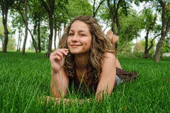 Attractive girl relaxes on grass Royalty Free Stock Image