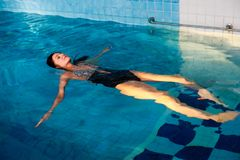Attractive girl relaxes in swimming pool Royalty Free Stock Image