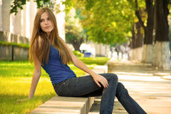 Attractive girl relaxing. Side portrait of attractive girl with long hair relaxing on wall on urban sidewalk or park with green trees in background Royalty Free Stock Photography