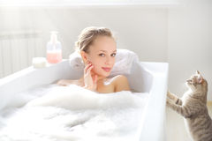 Attractive girl relaxing in bath. On light background Royalty Free Stock Photography