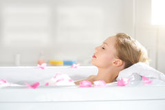 An Attractive girl relaxing in bath. On light background Royalty Free Stock Image